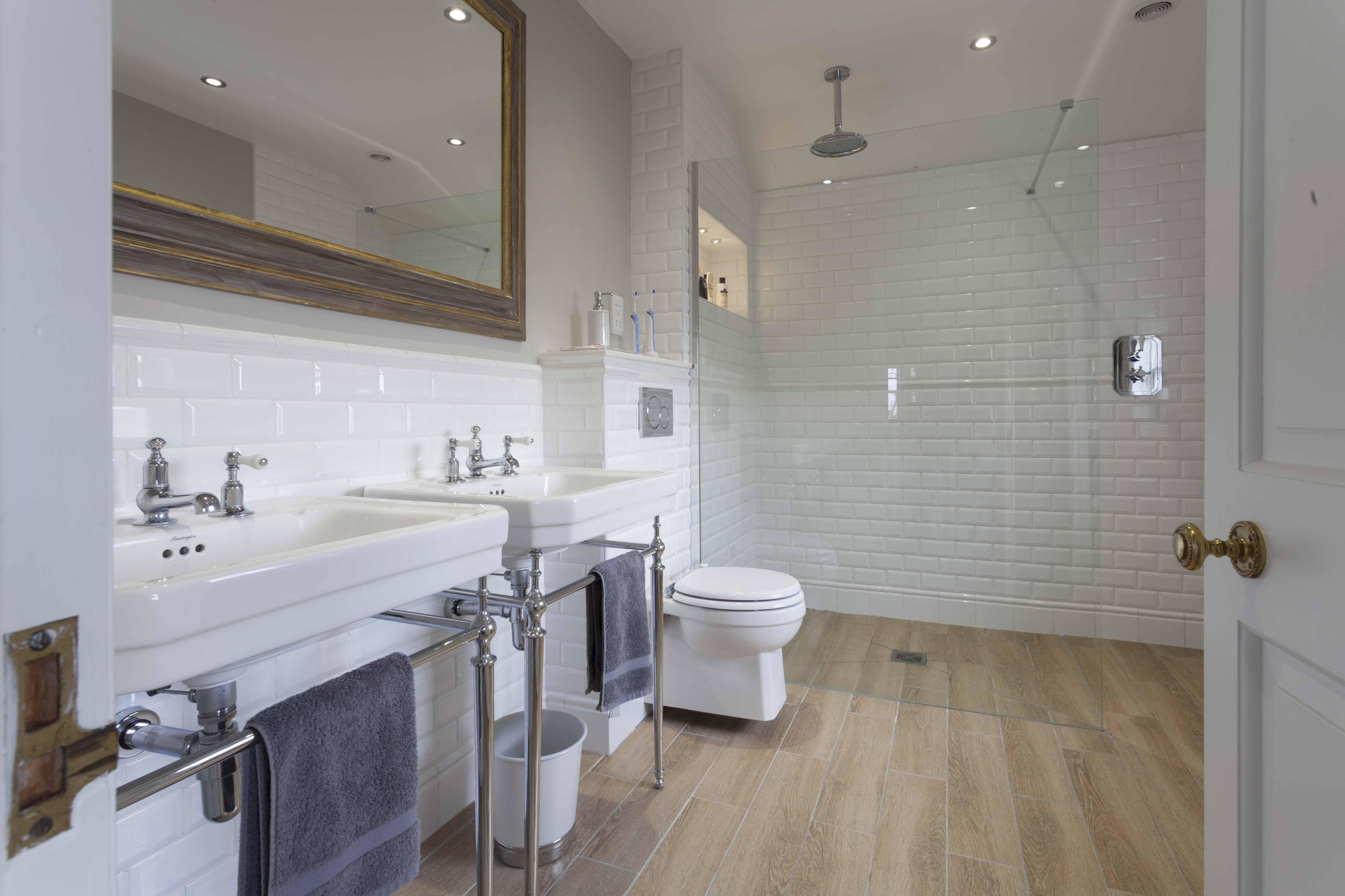 две раковины и стеклянная перегородка в большой ванной